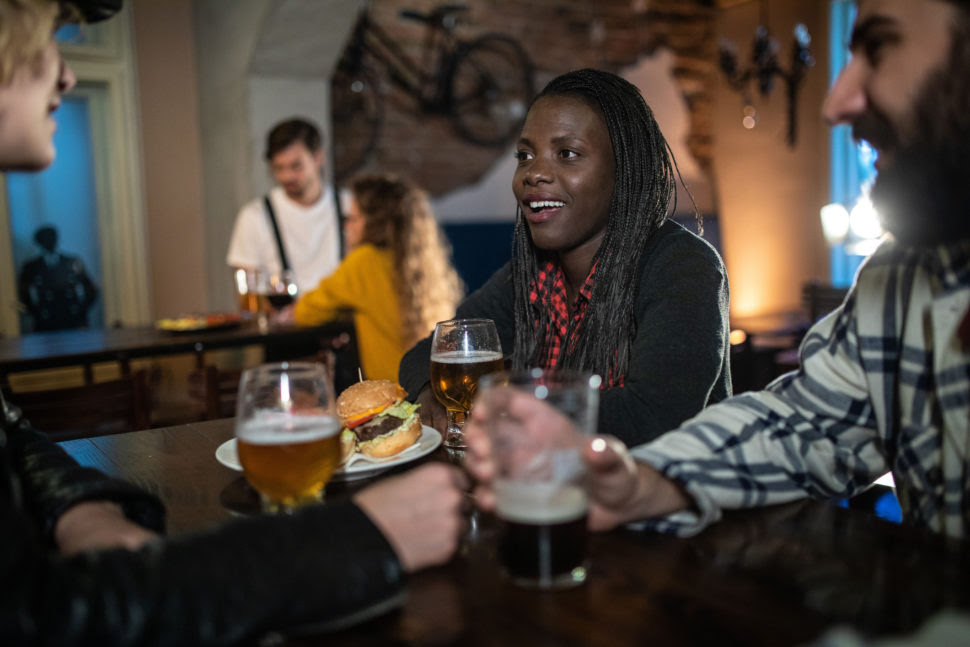 Cheerful Youth Drinking And Laughing Happily at Pub